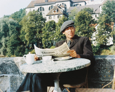 James Coburn reading a newspaper in a cafe in France in The Great Escape.