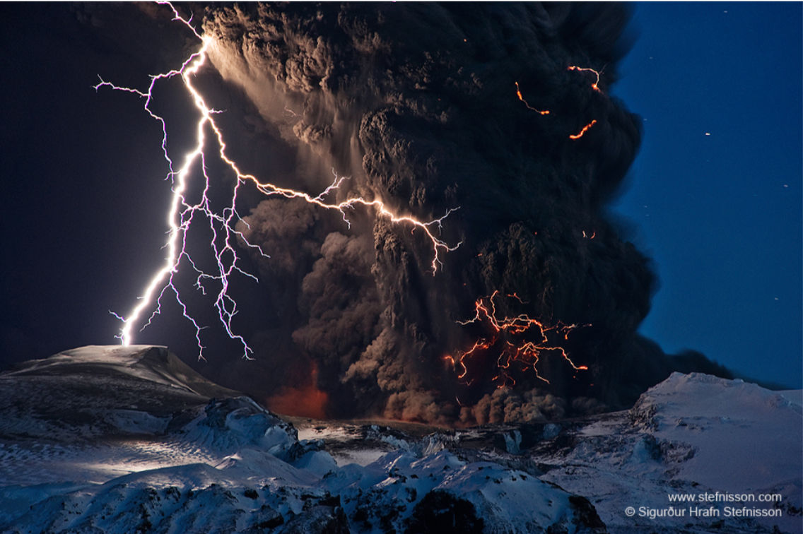 Image of lightening outside and inside dark clouds erupting out of a snow-clad volcano